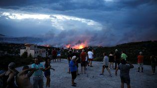 Des habitants observent le feu dévorer l'horizon, le 23 juillet 2018 à Rafina (Grèce). (ALKIS KONSTANTINIDIS / REUTERS)