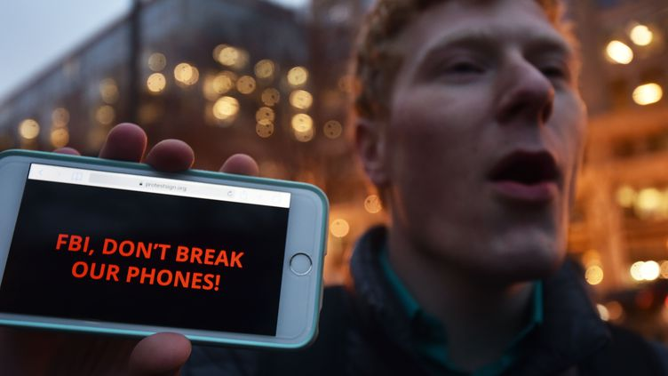 """Un homme manifeste en soutien à Apple, à Washington, le 23 février 2016, en affichant sur son téléphone un message adressé aux autorités : """"FBI, ne déchiffre pas nos téléphones."""" (PAUL J. RICHARDS / AFP)"""
