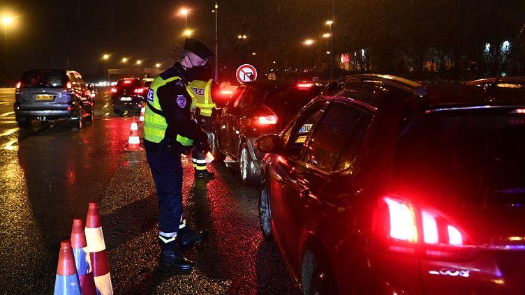 Un policier contrôle un automobiliste, le 31 janvier 2021, au péage du Buchelay dans les Yvelines, durant le couvre-feu. (CHRISTOPHE ARCHAMBAULT / AFP)