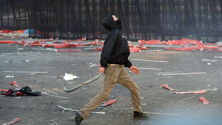 Un homme lance une barre de métal, pendant la soirée du PSG, le 13 mai 2013, à Paris. (FRANCK FIFE / AFP)