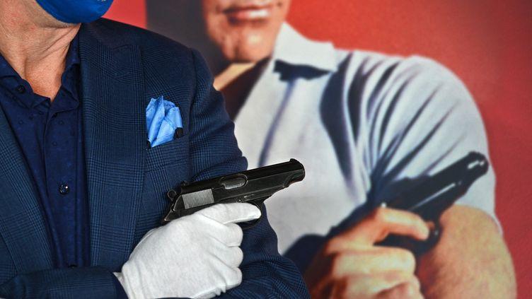 """Le pistolet de Sean Connery dans James Bond, présenté à la vente chez Julien's Auctions à Beverly Hills (USA), devant l'affiche de """"James Bond contre Dr No"""" (ROBYN BECK / AFP)"""