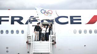 La maire de Paris, Anne Hidalgo, accompagnée par Tony Estanguet, président du comité d'organisation de Paris 2024, avec le drapeau olympique à son arrivée à Paris, lundi 9 août 2021. (STEPHANE DE SAKUTIN / AFP)