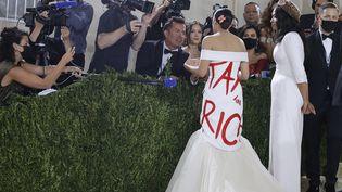 """La députée démocrate Alexandria Ocasio-Cortez (à gauche) portant une robe blanche marquée de l'écriture """"Tax the rich"""" sur le tapis rouge du Gala du Met à New York le 13 septembre 2021. (JUSTIN LANE / EPA)"""