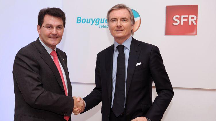 Olivier Roussat (à gauche), PDG de Bouygues Télécom, etJean-Yves Charlier, directeur général des activités télécoms deSFR, à Paris, le 2 février 2014. (ERIC PIERMONT / AFP)
