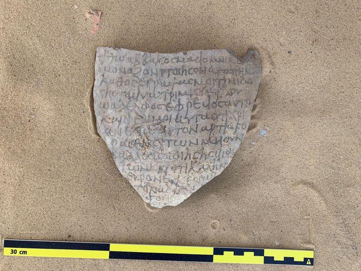 Fragment en argile contenant d'anciennes inscriptions chrétiennes, découvert dans le désert égyptien sur le site des vestiges (13 mars 2021) (EGYPTIAN MINISTRY OF ANTIQUITIES / AFP)