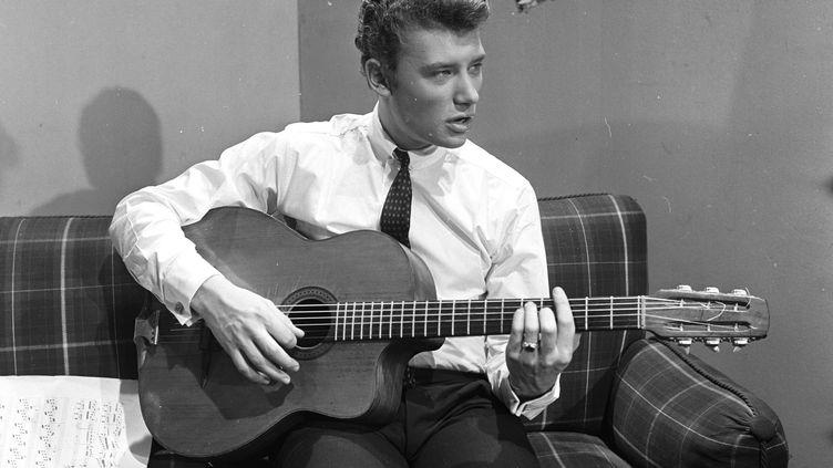Avec une tenue de jeune garçon sage, il pose lors d'une séance de portraits dans les studios de la télévisions à Cognacq Jay, à Paris le 22 décembre 1961. (JEAN CLAUDE MALLINJOD / INA)