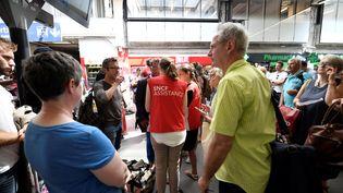 Les agents SNCF au secours des voyageurs désemparés à la gare Montparnasse, le 27 juillet 2018. (GERARD JULIEN / AFP)