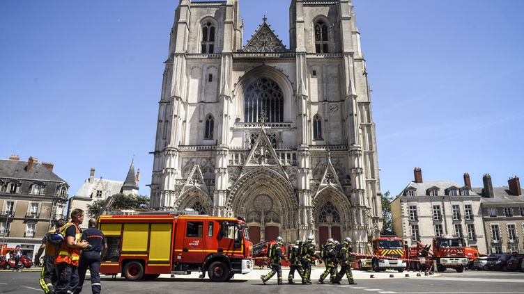 Des pompiers devant la cathédrale Saint-Pierre et Saint-Paul de Nantes (Loire-Atlantique), alors qu'elle a en partie brûlé, le 18 juillet 2020. (SEBASTIEN SALOM-GOMIS / AFP)