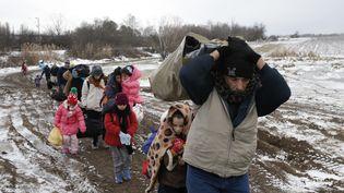 Des migrants à pied à travers champ sous le froid après avoir traversé la frontière de la Macédoine, près du village de Miratovac (Serbie), le 18 Janvier 2016. (MARKO DJURICA / REUTERS)