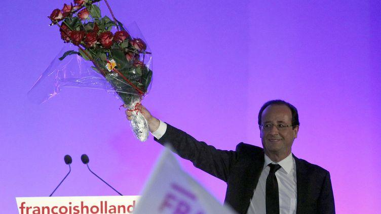 François Hollande célèbre sa victoire à l'élection présidentielle et brandit un bouquet de roses rouges sur la scène installée à Tulle (Corrèze), le 6 mai 2012. (REGIS DUVIGNAU / REUTERS)