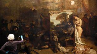"""Une restauratrice d'art travaille sur """"L'Atelier du peintre"""" de Gustave Courbet, au musée d'Orsay, à Paris, le 2 décembre 2014. (PATRICK KOVARIK / AFP)"""