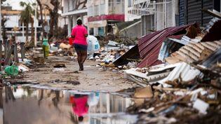 Unehabitante de Saint-Martin porte de l'eau dans une rue de Marigot, le 12 septembre 2017, après le passage de l'ouragan Irma sur l'île. (MARTIN BUREAU / AFP)