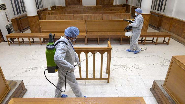 Des agents de santé désinfectent une salle de tribunal à L'Ariana, près de Tunis, le 12 mars 2020. (FETHI BELAID / AFP)