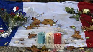 Des bougies, des fleurs et le drapeau français, déposés près du Bataclan, à Paris, le 18 novembre 2015. (DOMINIQUE FAGET / AFP)
