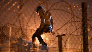 Un migrant tente d'escalader une barrière de sécurité à Calais (Pas-de-Calais), le 3 août 2015. (MUSTAFA YALCIN / ANADOLU AGENCY / AFP)