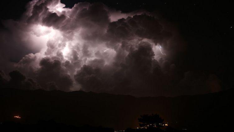 Un éclair lors d'une tempête sur la vallée du Taravo et le village de Petreto-Bicchisano (Corse-du-Sud), le 15 août 2018. (PASCAL POCHARD-CASABIANCA / AFP)