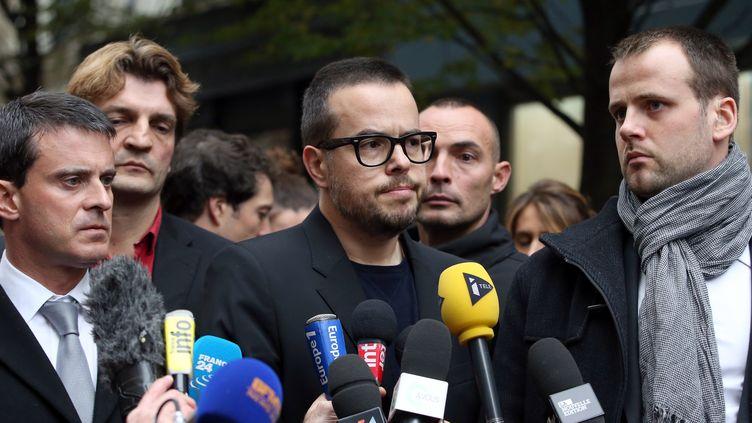 """Nicolas Demorand,directeur de publication de """"Libération"""",et le ministre de l'Intérieur, le 18 novembre 2013 devant le siège de Libé, à Paris. (KENZO TRIBOUILLARD / AFP)"""