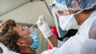 Un homme passe un test PCR de dépistage du coronavirus dans une tente sur le parvis de l'hôtel de ville, à Paris, le 4 septembre 2020. (VOISIN / PHANIE / AFP)