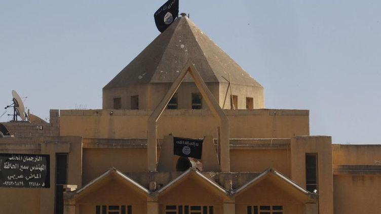 Le drapeau de l'Etat islamique sur l'Eglise des martyrs de Raqqa (Syrie), le 27 septembre 2013. (STRINGER / REUTERS )