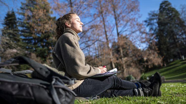 Une étudiante profite du soleil dans un parc de Fribourg (Allemagne), le 15 janvier 2020. (PATRICK SEEGER / DPA)