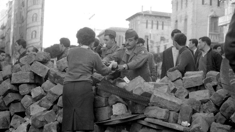 """Une femme apporte du café à des émeutiers favorables à l'Algérie française pendant la """"Semaine des barricades"""" (24 janvier-1er février) à Alger. (JEAN-CLAUDE COMBRISSON / AFP)"""