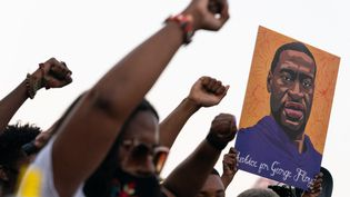 Des manifestants lèvent leur poing et brandissent un portrait de George Floyd, à l'annonce du verdict contre Derek Chauvin, le 20 avril 2021, à Atlanta. (ELIJAH NOUVELAGE / AFP)