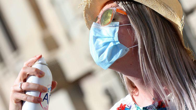Une femme avec chapeau, lunettes de soleil et masque,se rafraîchitavec un brumisateur, à Colmar (Haut-Rhin), le 15 septembre 2020. (VANESSA MEYER / MAXPPP)