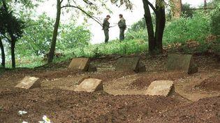 Une photo datant de mai 1997, sur laquelle des soldats algériens gardent les tombes des sept moines, à Tibéhirine (Algérie). ( AFP )