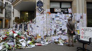 """Un homme se recueille devant un mémorial improvisé à proximité de l'ancienne rédaction de """"Charlie Hebdo"""", à Paris, quelques jours après l'attaque du 7 janvier 2015. (BERTRAND GUAY / AFP)"""