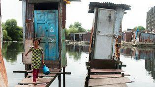 Eriam Sheikh, âgée de 7 ans, vient de sortir d'une cabine de toilettes sur pilotis, dans le quartier Rafiq Nagar, à Mumbai, en Inde. (UNICEF / MANPREET ROMANA)