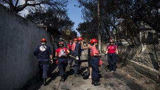 Des équipes de secours à Mati, en Grèce, le 25 juillet 2018. (ANGELOS TZORTZINIS / AFP)