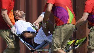 Yohann Diniz est évacué sur un fauteuil roulant à la fin du 50 km marche, aux Jeux olympiques de Rio (Brésil), le 19 août 2016. (JULIEN CROSNIER / DPPI MEDIA / AFP)