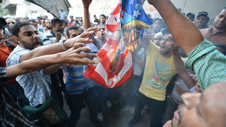 Des Egyptiens protestent devant l'ambassade américaine au Caire (Egypte) en brûlant un drapeau des Etats-Unis, le 12 septembre 2012. (KHALED DESOUKI / AFP)