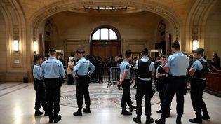 Des policiers montent la garde devant le tribunal correctionnel de Paris, vendredi 22 septembre 2017. Neuf prévenus étaient jugés pour avoir frappé un policier et mis le feu à son véhicule en mai 2016. (LIONEL BONAVENTURE / AFP)