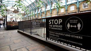 Un panneau sur la distanciation sociale à observer pendant l'épidémie de Covid-19, à Covent garden, dans le centre de Londres, le 29 octobre 2020. (KATE GREEN / ANADOLU AGENCY / AFP)