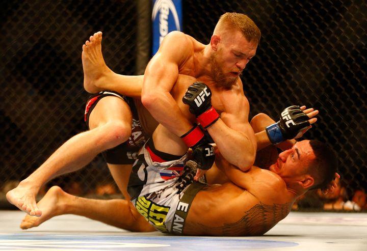 Conor McGregor prend le dessus sur son adversaire, Max Holloway, lors d'un combat organisé au TD Garden de Boston (Etats-Unis), le 17 août 2013. (JARED WICKERHAM / GETTY IMAGES NORTH AMERICA / AFP)