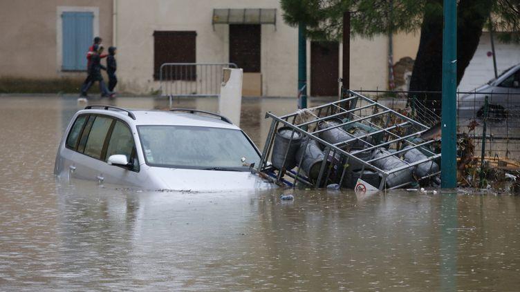 Une voiture et des bouteilles de gaz sont submergées par les eaux, le 24 novembre 2019, au Muy (Var), après les intempéries survenues dans le Sud-Est. (VALERY HACHE / AFP)