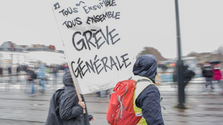 """Des grévistes portent une pancarte """"Grève générale"""" dans une rue de Nantes (Loire-Atlantique).  (LOIC VENANCE / AFP)"""