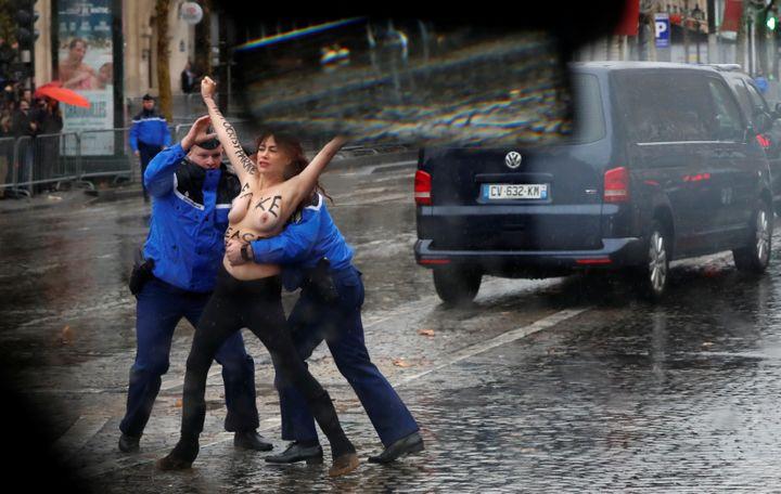 Deux gendarmes maîtrisent une militante Femen, le 11 novembre 2018, sur les Champs-Elysées, à Paris. (CARLOS BARRIA / REUTERS)