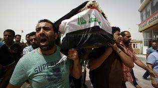 Des hommes portent le corps d'une victime de l'attentat commis à Bagdad (Irak), le 3 juillet 2016,lors d'une procession dans la ville sainte chiite de Najaf. (HAIDAR HAMDANI / AFP)