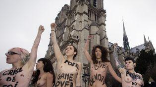 Des militantes féministes de l'organisation Femen célèbrent la démission du pape devant la cathédrale Notre-Dame à Paris, le 12 février 2013. (JOEL SAGET / AFP)
