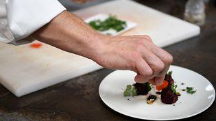 Une assiette en train d'être dresséedans lacuisine d'un restaurant (illustration). (JEAN-PIERRE CLATOT / AFP)