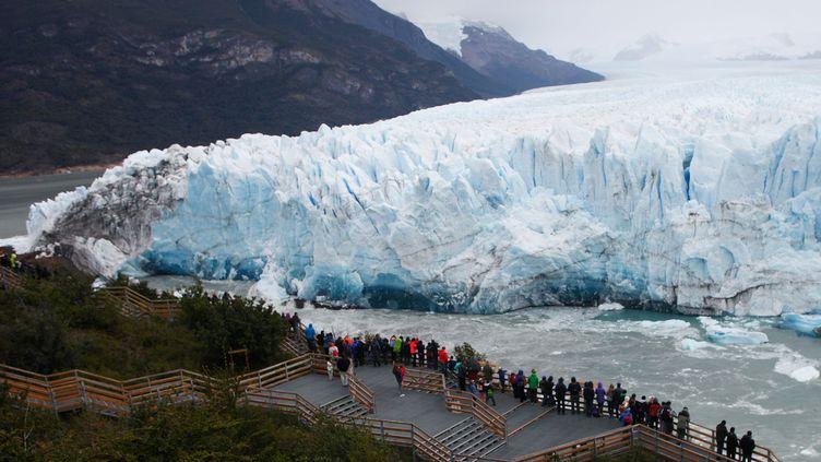 Des touristes rassemblés pour assister à la rupture du glacier Perito Moreno,en Patagonie (Argentine), le 10 mars 2018. (WALTER DIAZ / AFP)
