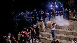 Une grenade assourdissante explose près de Palestiniens lors des heurts avec la police israélienne, à Jérusalem, le 8 mai 2021. (SHANG HAO / XINHUA / REUTERS)