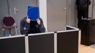 L'ancien infirmier Niels Högel, accusé d'avoir perpétré une centaine de meurtres, se camoufle la tête lors de l'ouverture de son procès, le 30 octobre 2018, à Oldenbourg(Allemagne). (JULIAN STRATENSCHULTE / DPA / AFP)