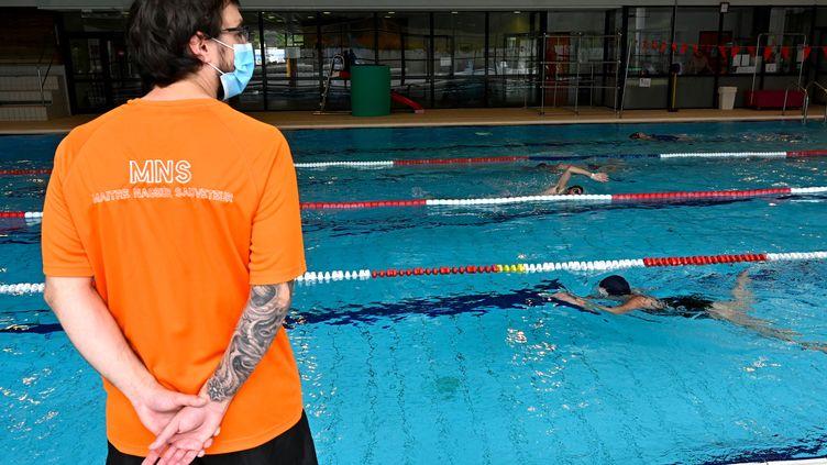 Un maître-nageur portant un masque dans une piscine publique àChartres-de-Bretagne (Ille-et-Vilaine), le 4 juin 2020. (DAMIEN MEYER / AFP)