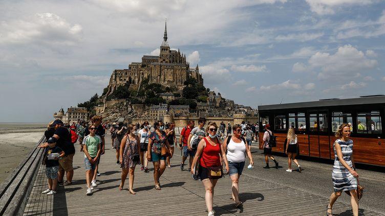 Des touristes marchent devant le Mont-Saint-Michel en Normandie, le 22 juillet 2021. (SAMEER AL-DOUMY / AFP)