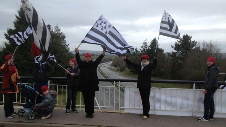 """Des """"bonnets rouges"""" brandissent des drapeaux, sur un pont enjambant une voie express, en Bretagne. (STEPHANE IZAD - FRANCE 3 BRETAGNE)"""