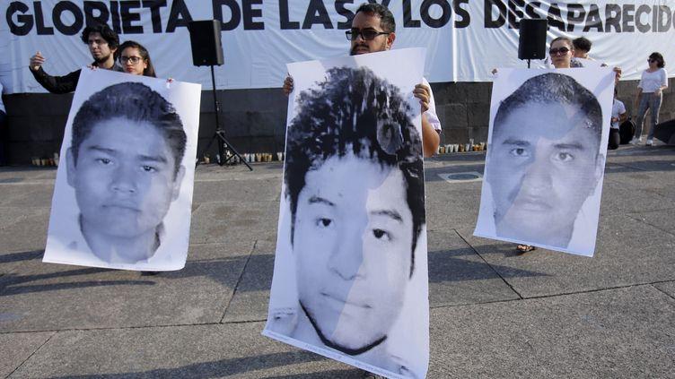 Les visages des trois étudiants disparus sont brandis lors d'une manifestation, le 19 avril 2018 à Guadalajara (Mexique). (ULISES RUIZ / AFP)