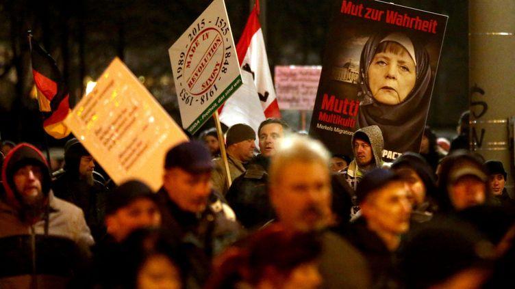 Des manifestants anti-islam brandissent des pancartes sur lesquelles la chancelière Merkel porte un voile islamique, le 21 janvier 2015, à Leipzig (Allemagne). (MEHMET KAMAN / ANADOLU AGENCY / AFP)